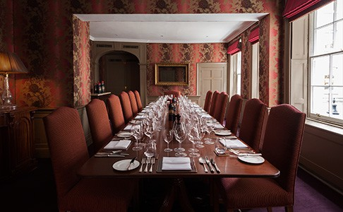 Long table laid out for dinner in the plush Townhouse room in daylight