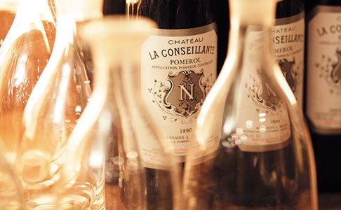 Close-up shot of bottles of Pomerol and decanters in candlelight