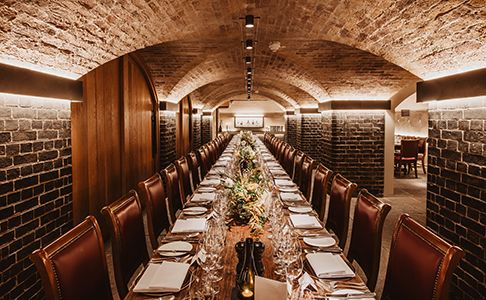 Napoleon Cellar with long table laid out for dinner with cutlery and wine glasses