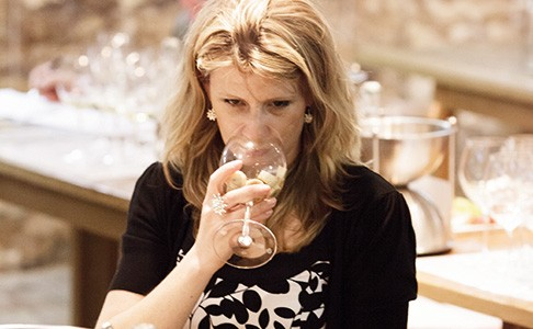 Woman sniffing a substance in a wine glass at a wine-tasting classEvening Wine Schools